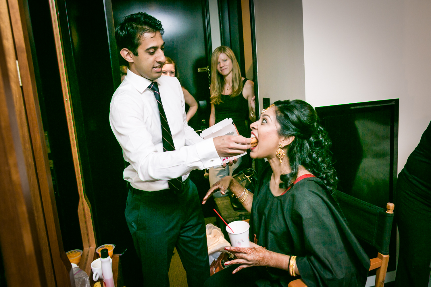 Brother feeding bride while she is getting ready
