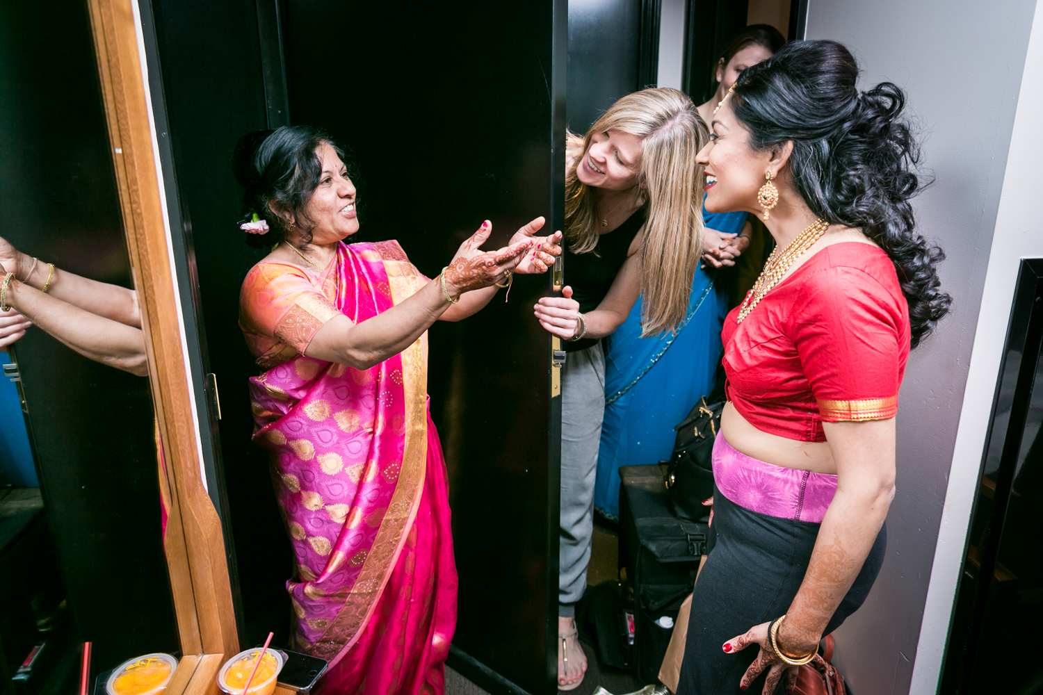 Mother in Indian sari greeting bride and bridal party