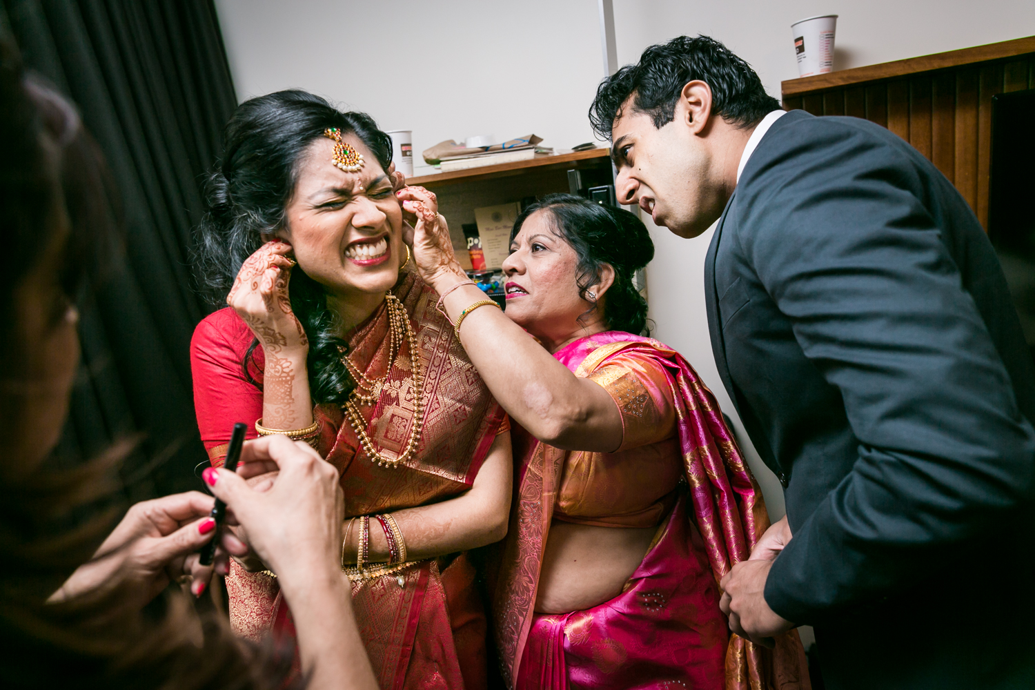 Mother and brother helping Indian bride put in her earrings