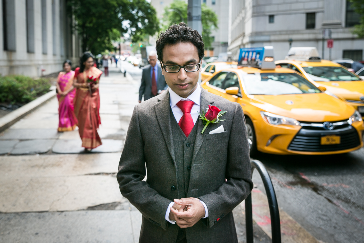 Groom waiting for bride on sidewalk during first look