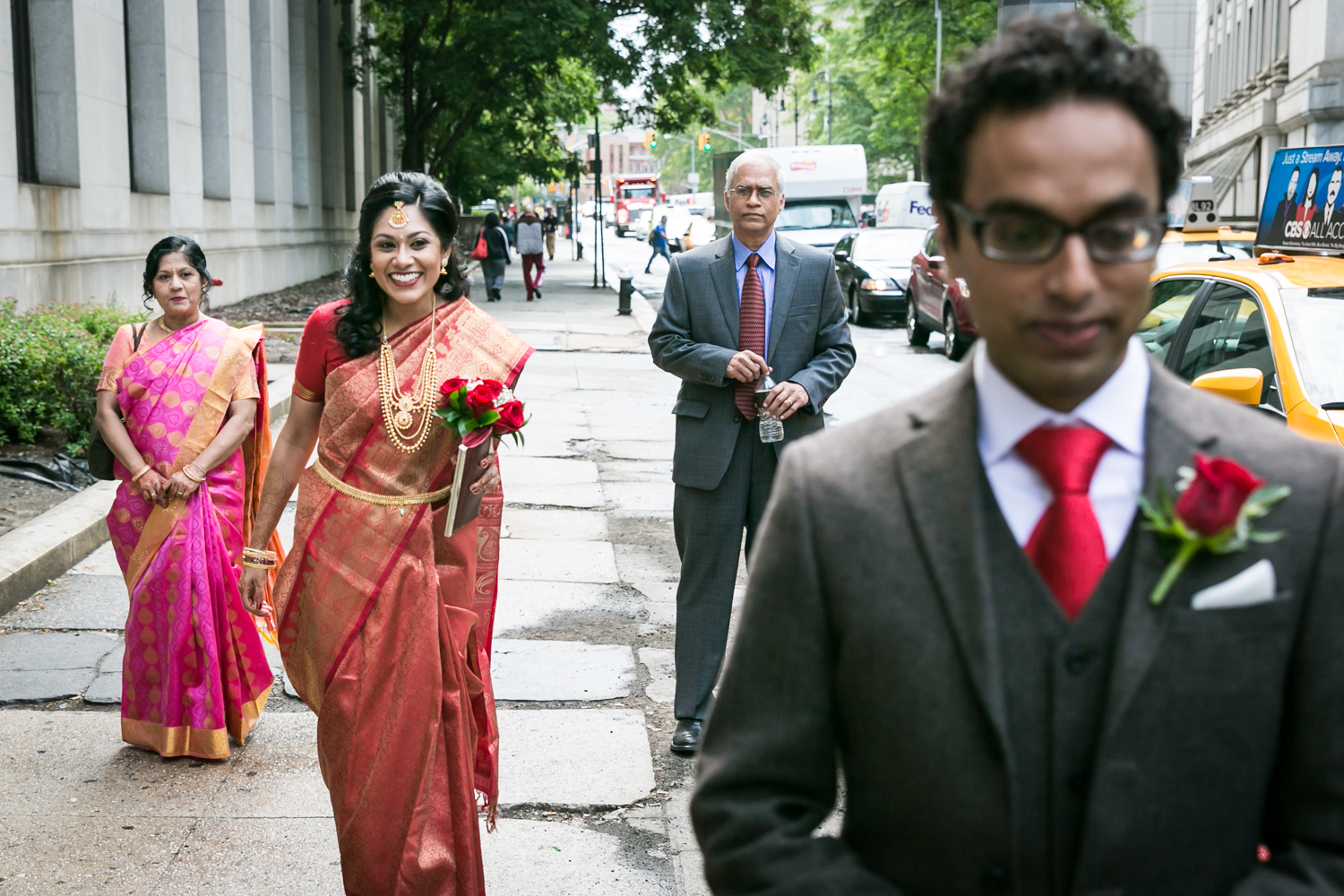 Indian bride wearing sari about to approach groom on sidewalk for first look