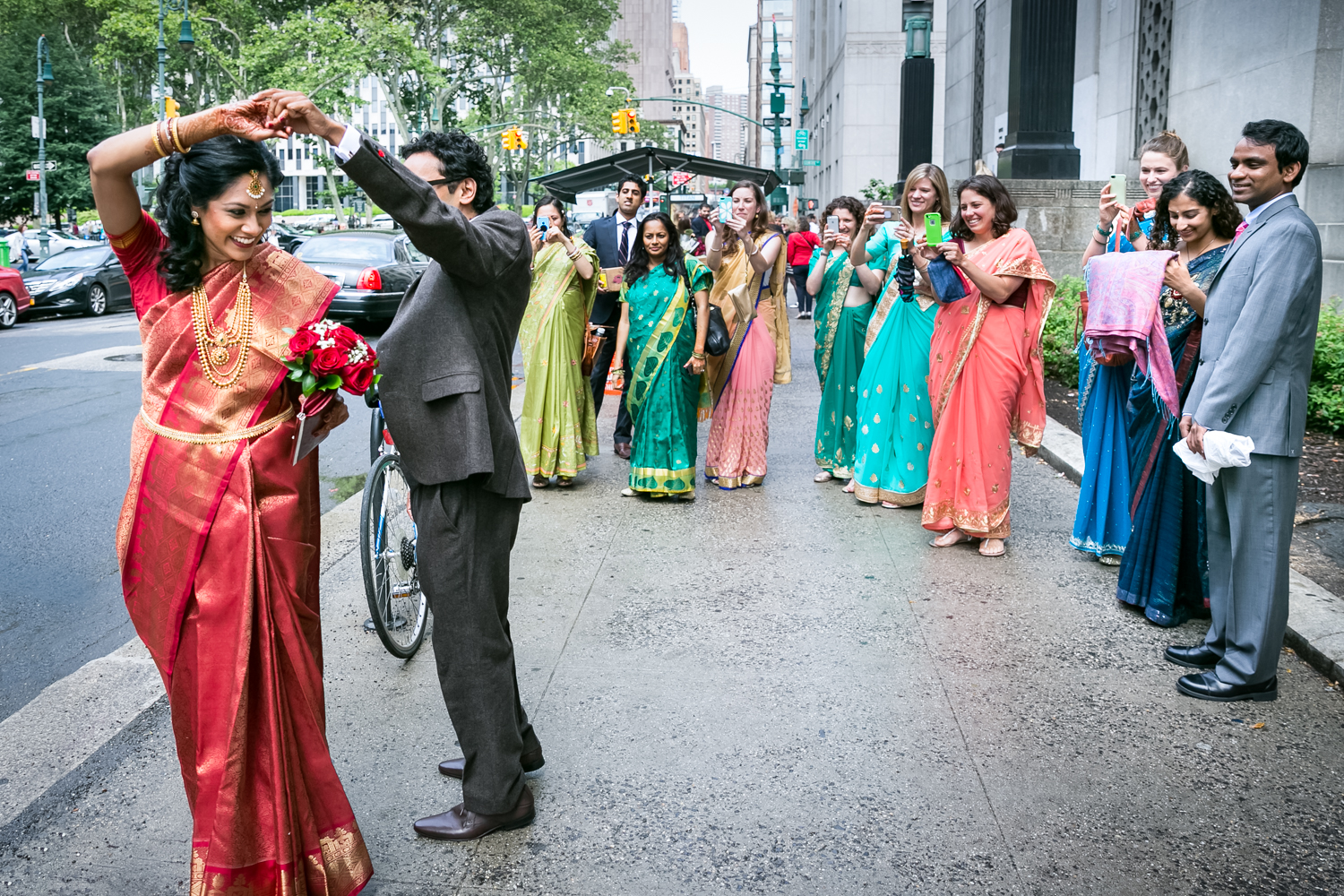 Bride and groom dancing in front of bridal party wearing traditional saris