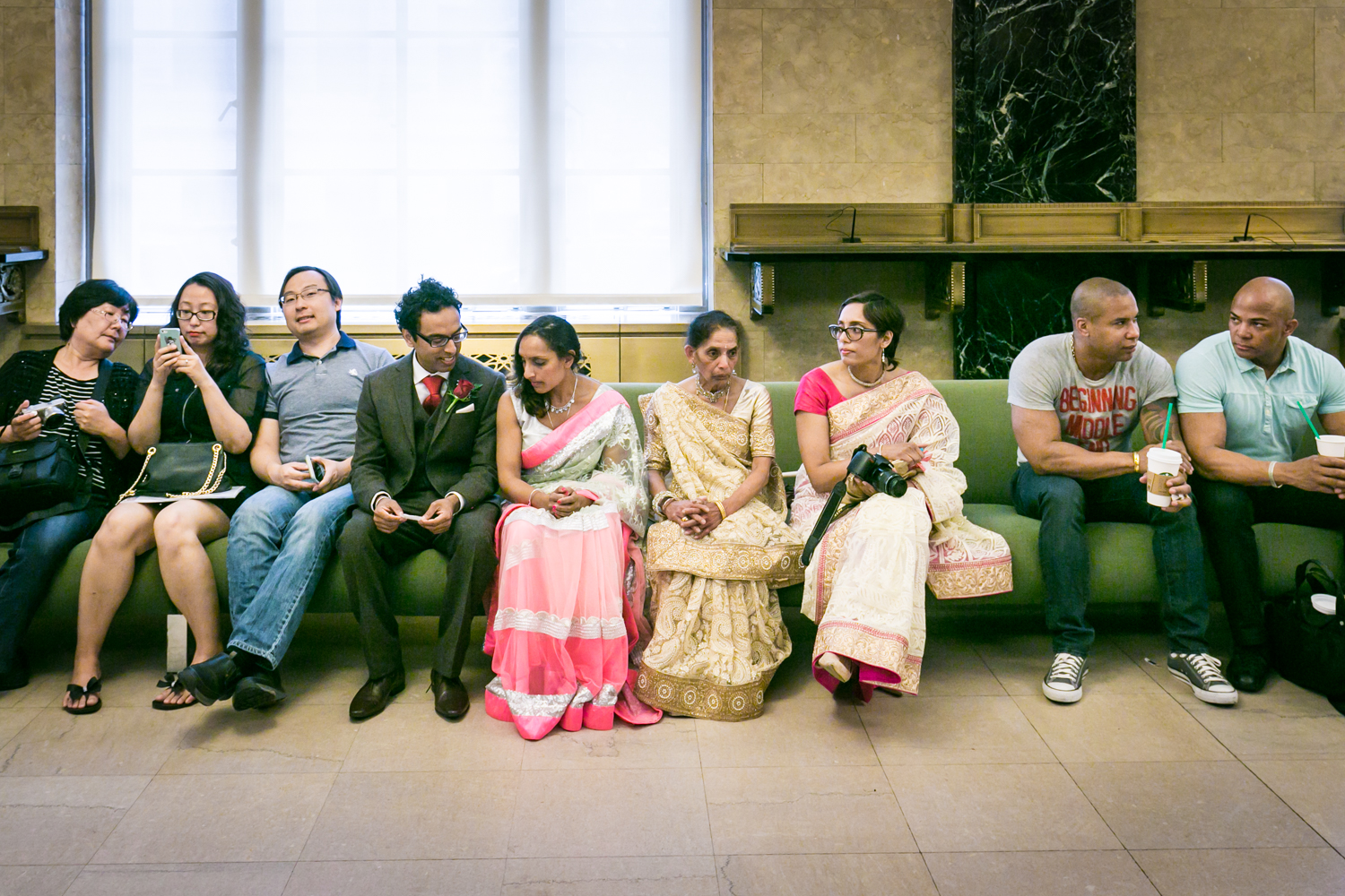 Bridal party wearing traditional saris waiting on bench at a NYC City Hall Indian wedding