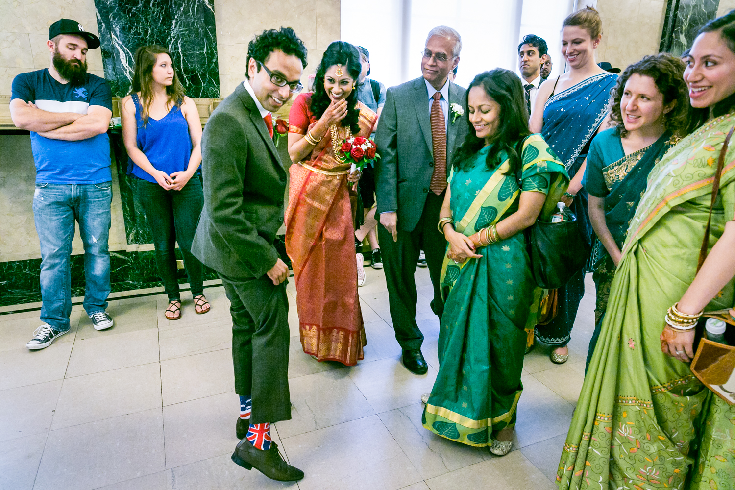 Groom showing off socks in front of bridal party at a NYC City Hall Indian wedding