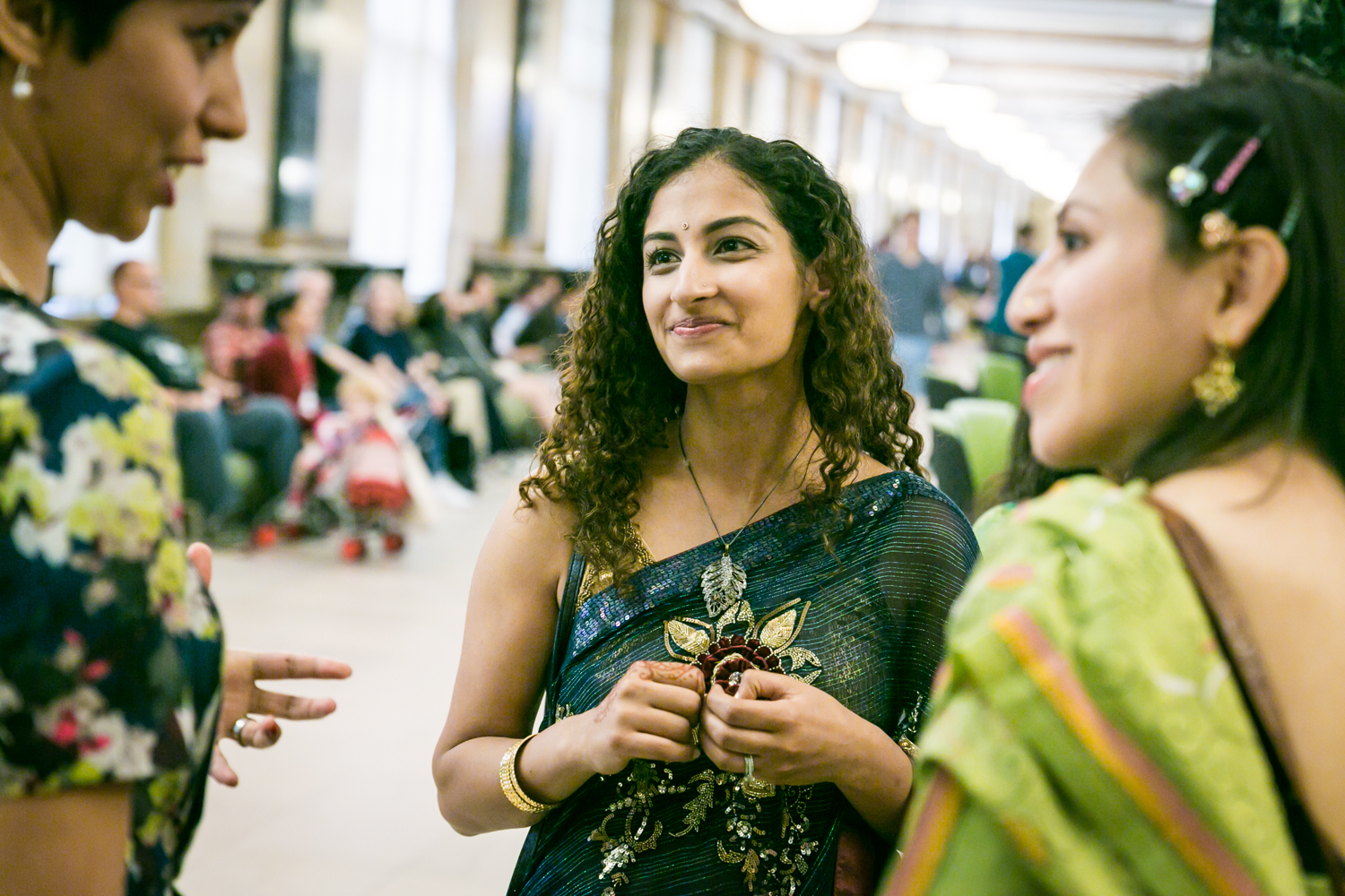 Three women wearing saris and talking at a NYC City Hall Indian wedding