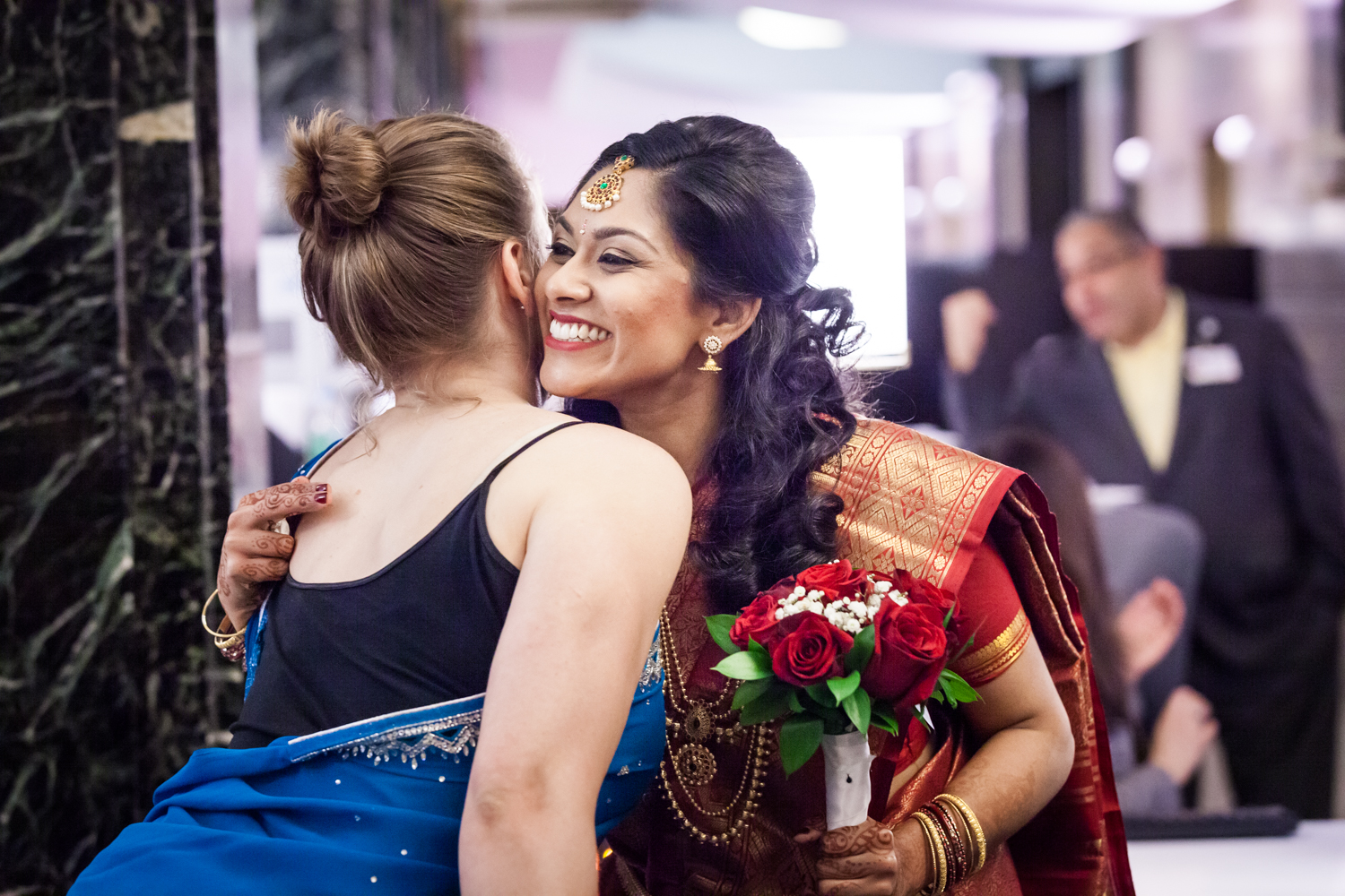 Indian bride hugging woman wearing sari at a NYC City Hall Indian wedding