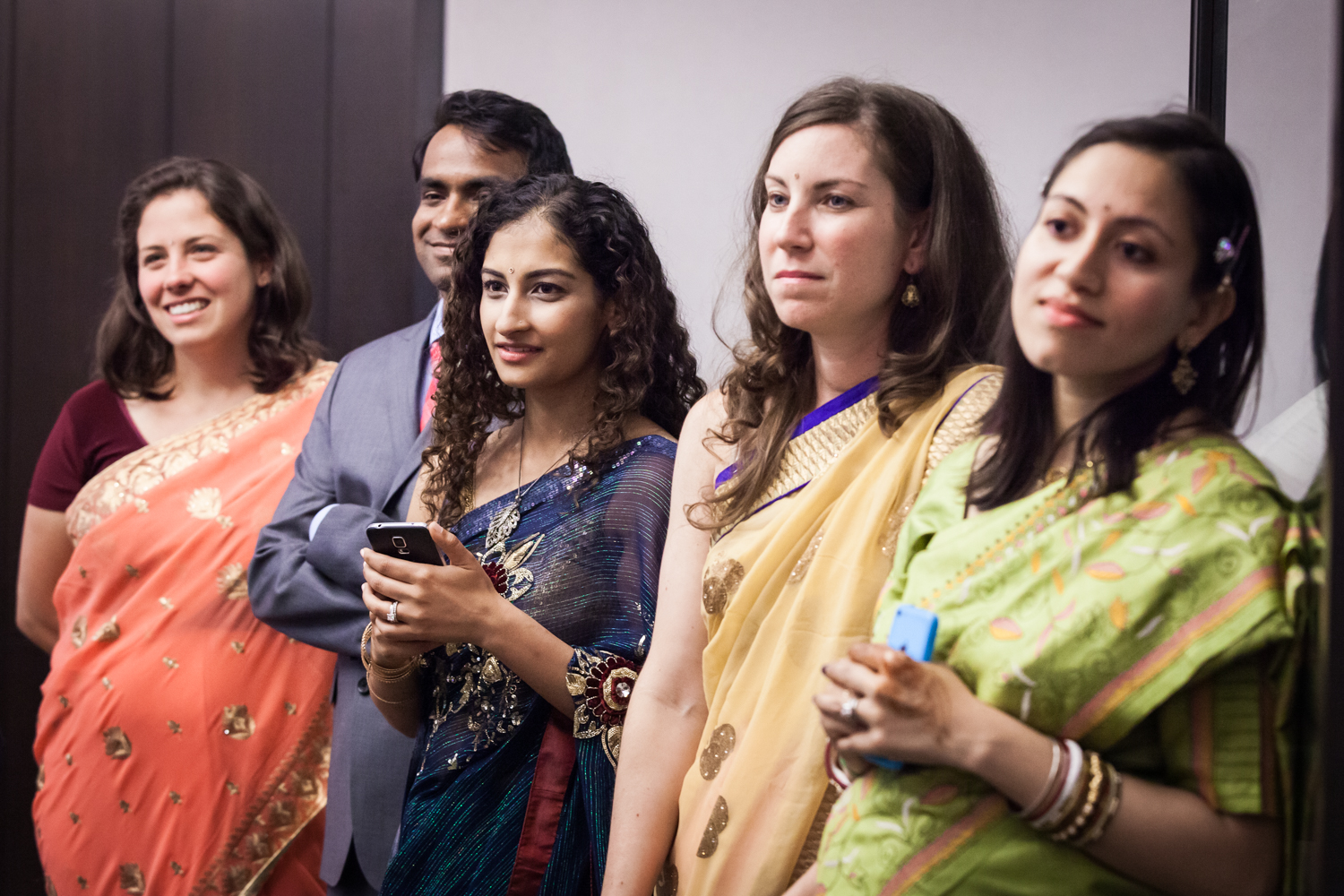 Guests wearing Indian saris listening to ceremony at a NYC City Hall Indian wedding