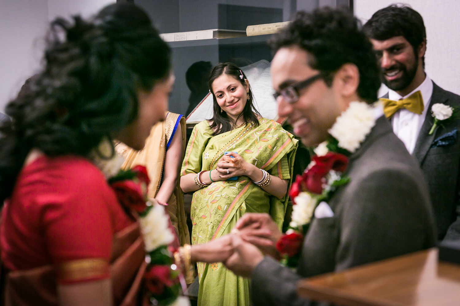 Woman wearing green sari watching groom put ring on bride's finger at a NYC City Hall Indian wedding