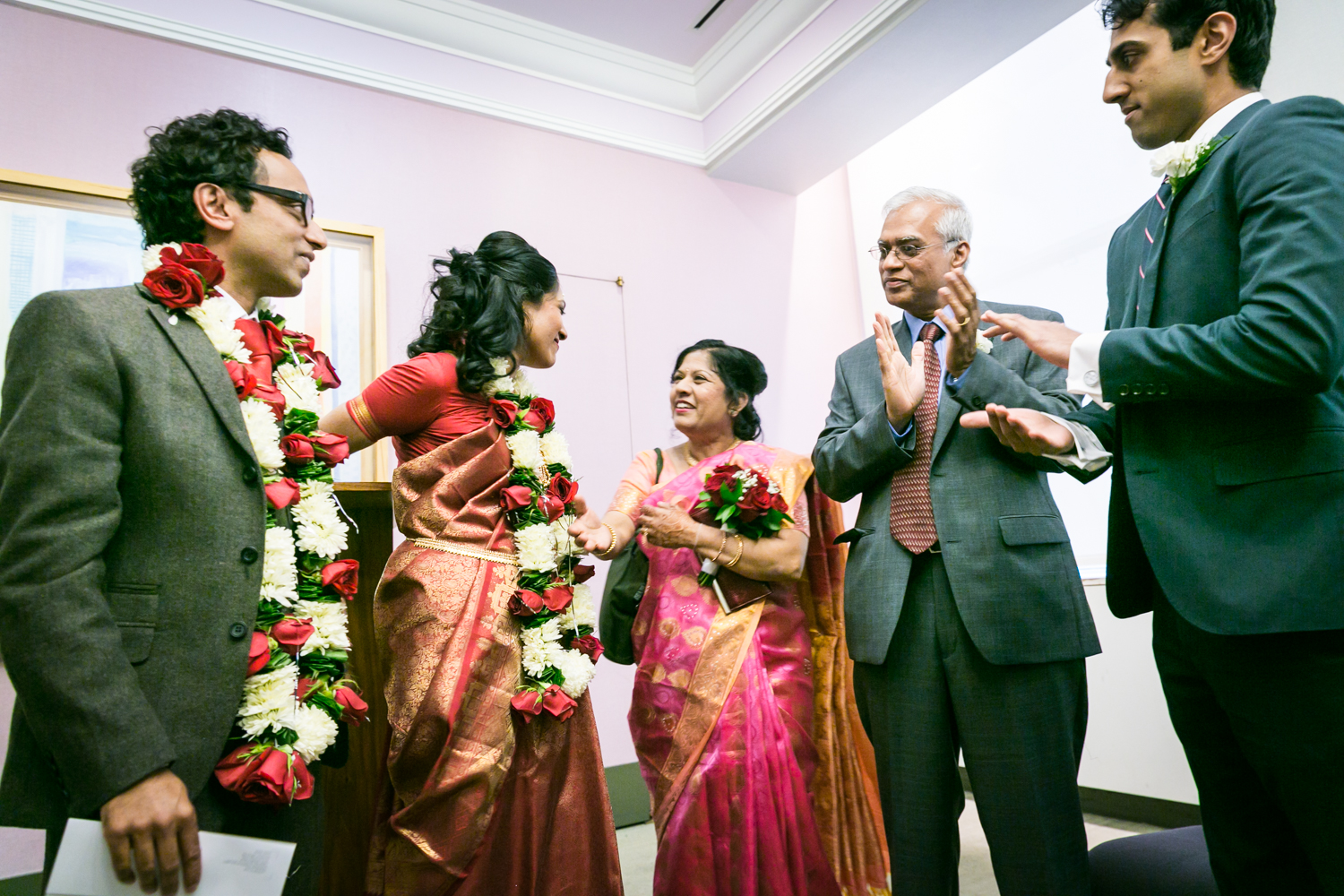 Bride and groom talking with family at a NYC City Hall Indian wedding