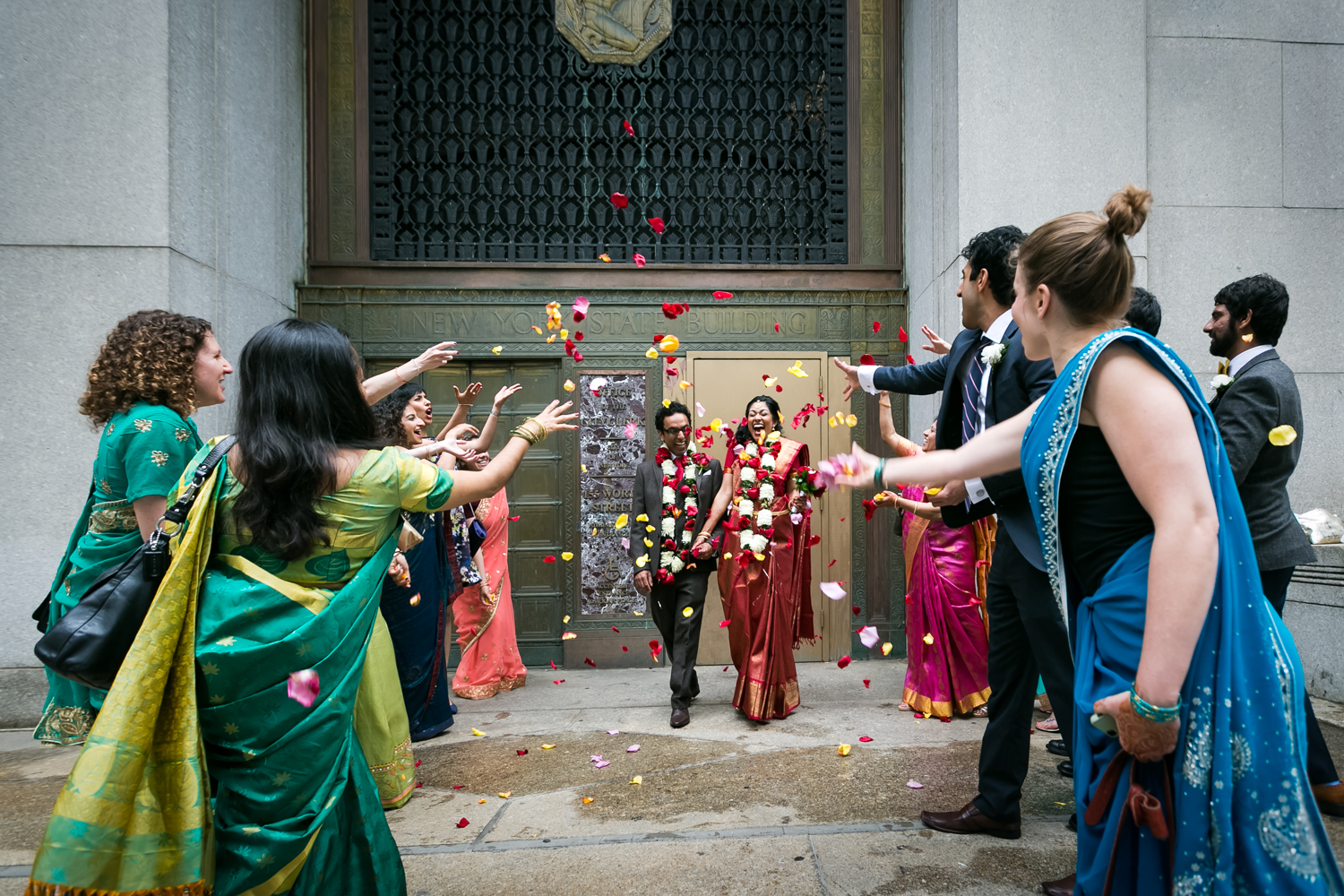 Bridal party wearing saris throwing rose petals at Indian bride and groom at a NYC City Hall Indian wedding