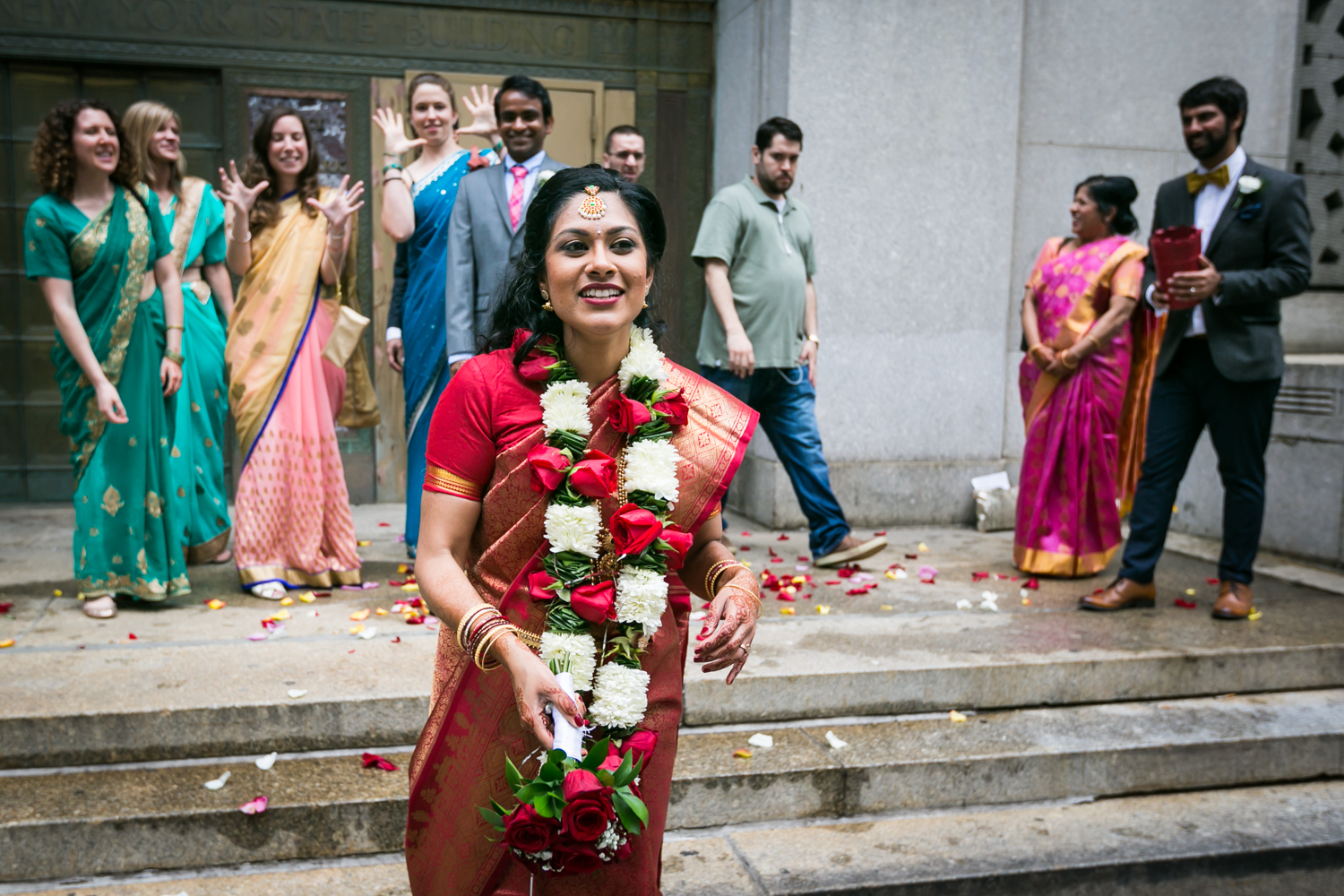 Indian bride in red sari about to throw bouquet at a NYC City Hall Indian wedding