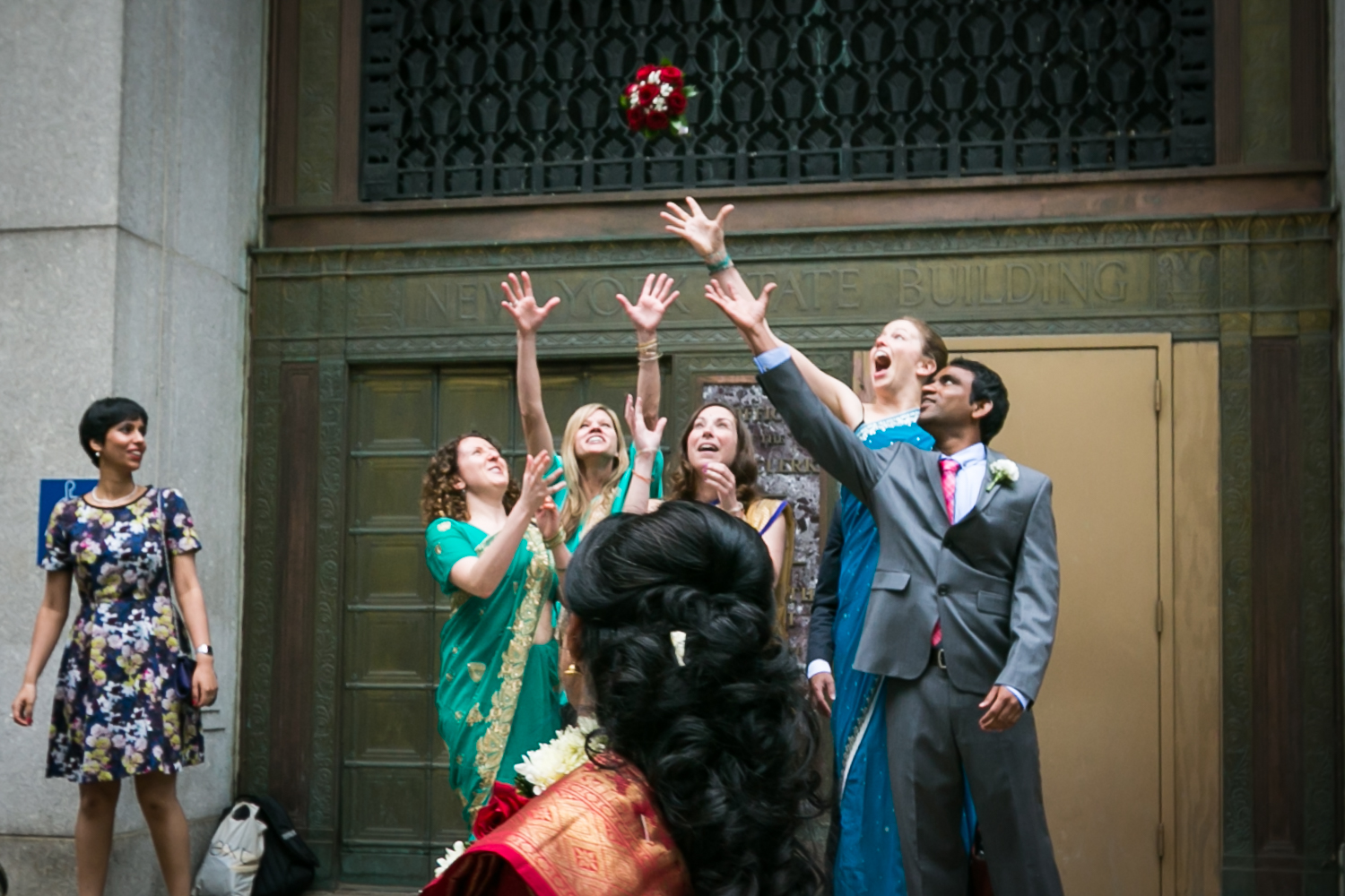 Bridal party wearing Indian saris and catching bouquet at a NYC City Hall Indian wedding
