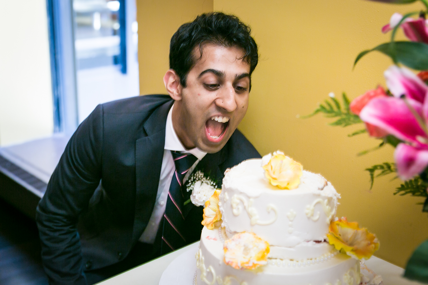 Man about to bite into wedding cake at a NYC City Hall Indian wedding