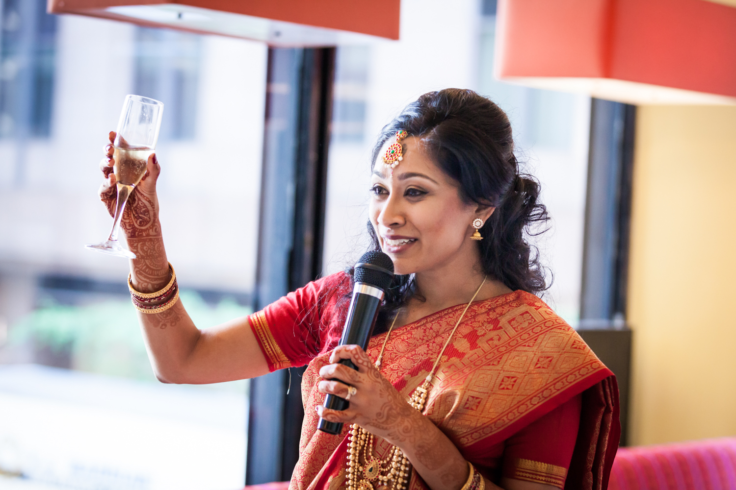 Indian bride in red sari holding up champagne glass at a NYC City Hall Indian wedding