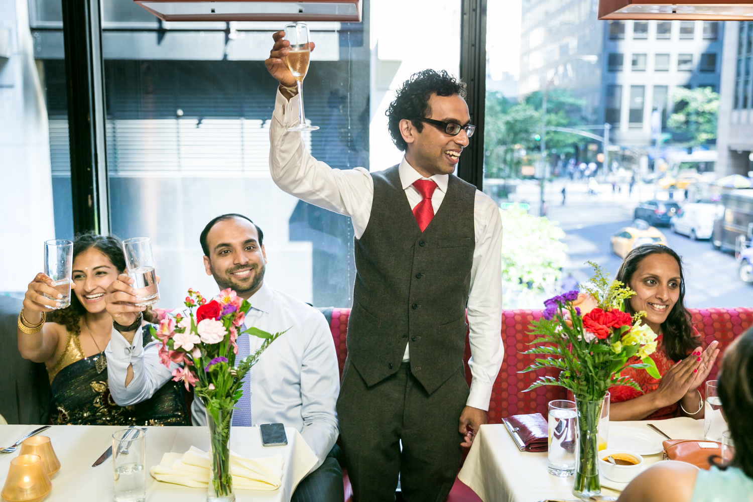 Groom standing between tables of guests holding glass of champagne