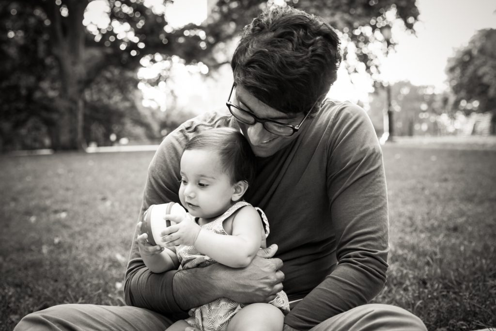 Black and white photo of father playing with toddler in grass