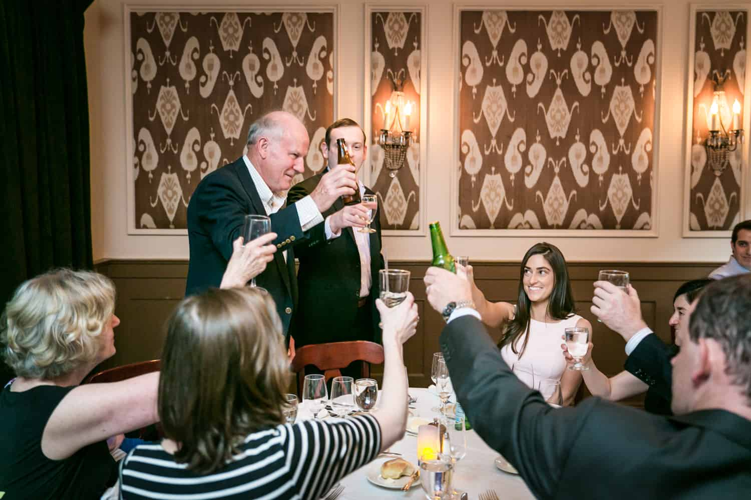 Family making a toast at a table at a Hoboken rehearsal dinner