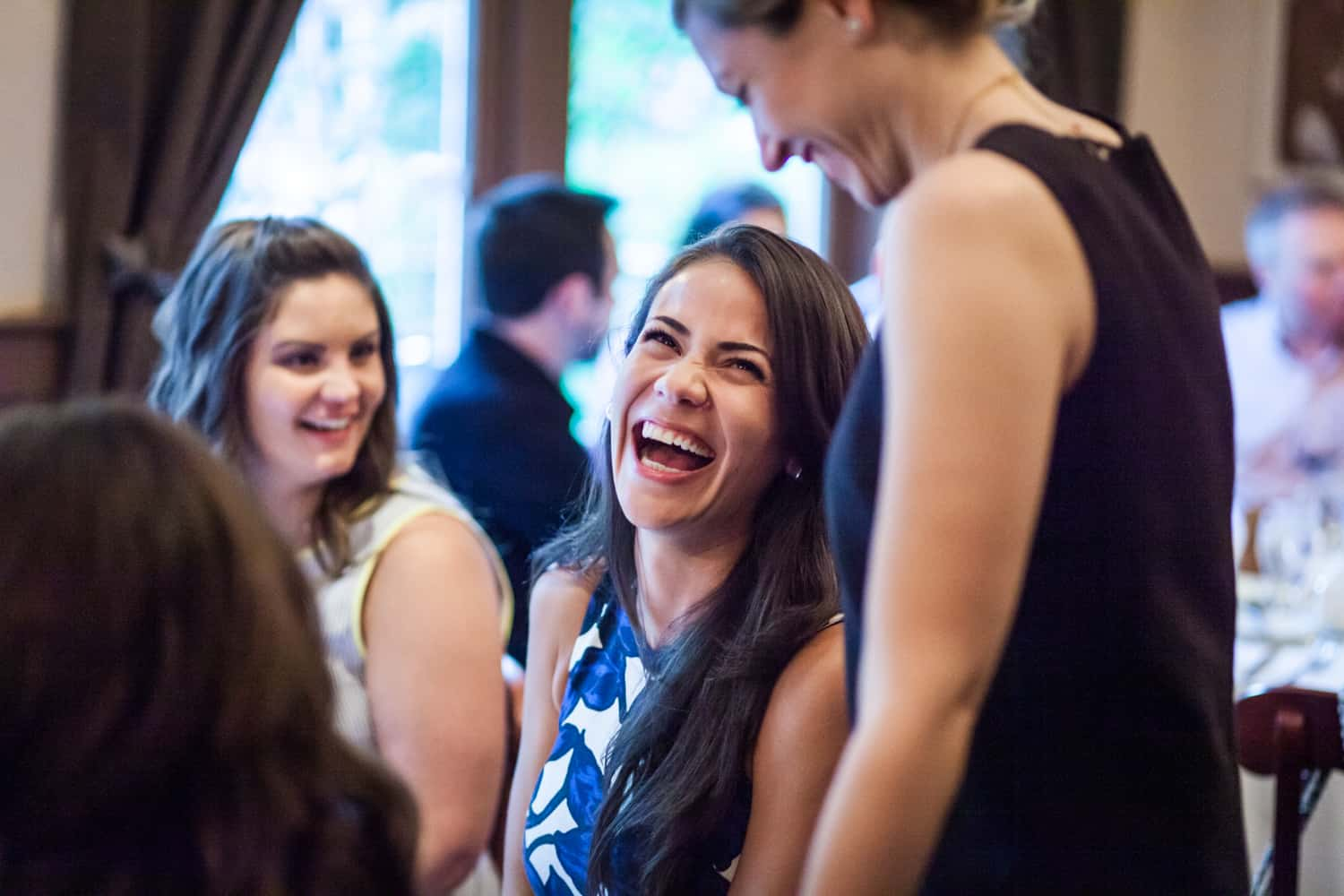 Female guest laughing with other guests at a rehearsal dinner