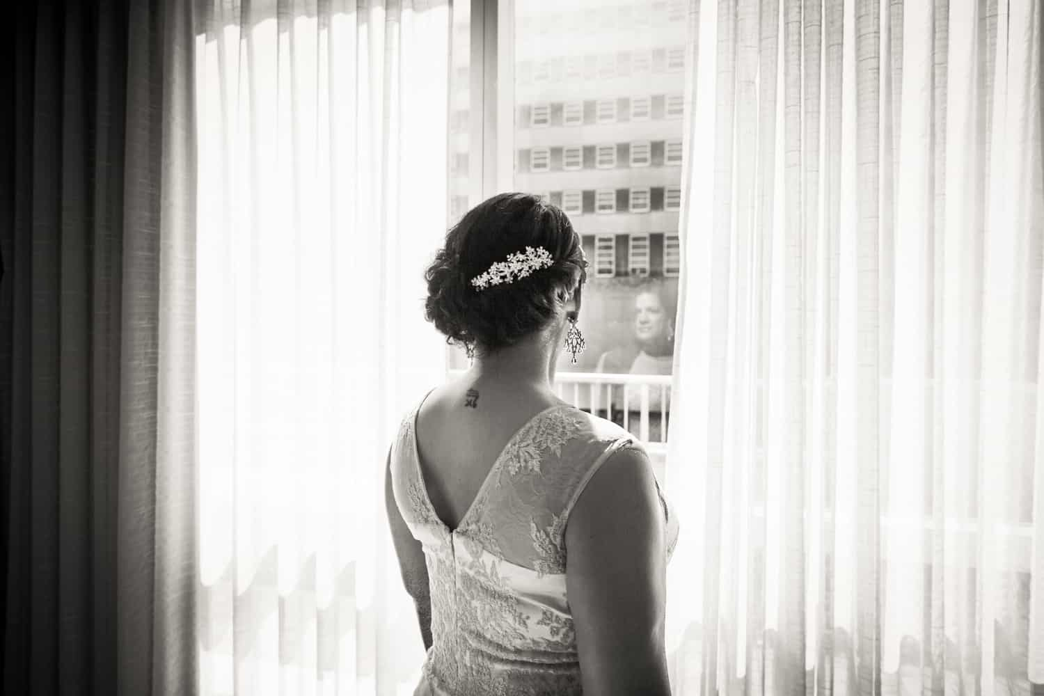 Black and white photo of bride looking out of hotel window