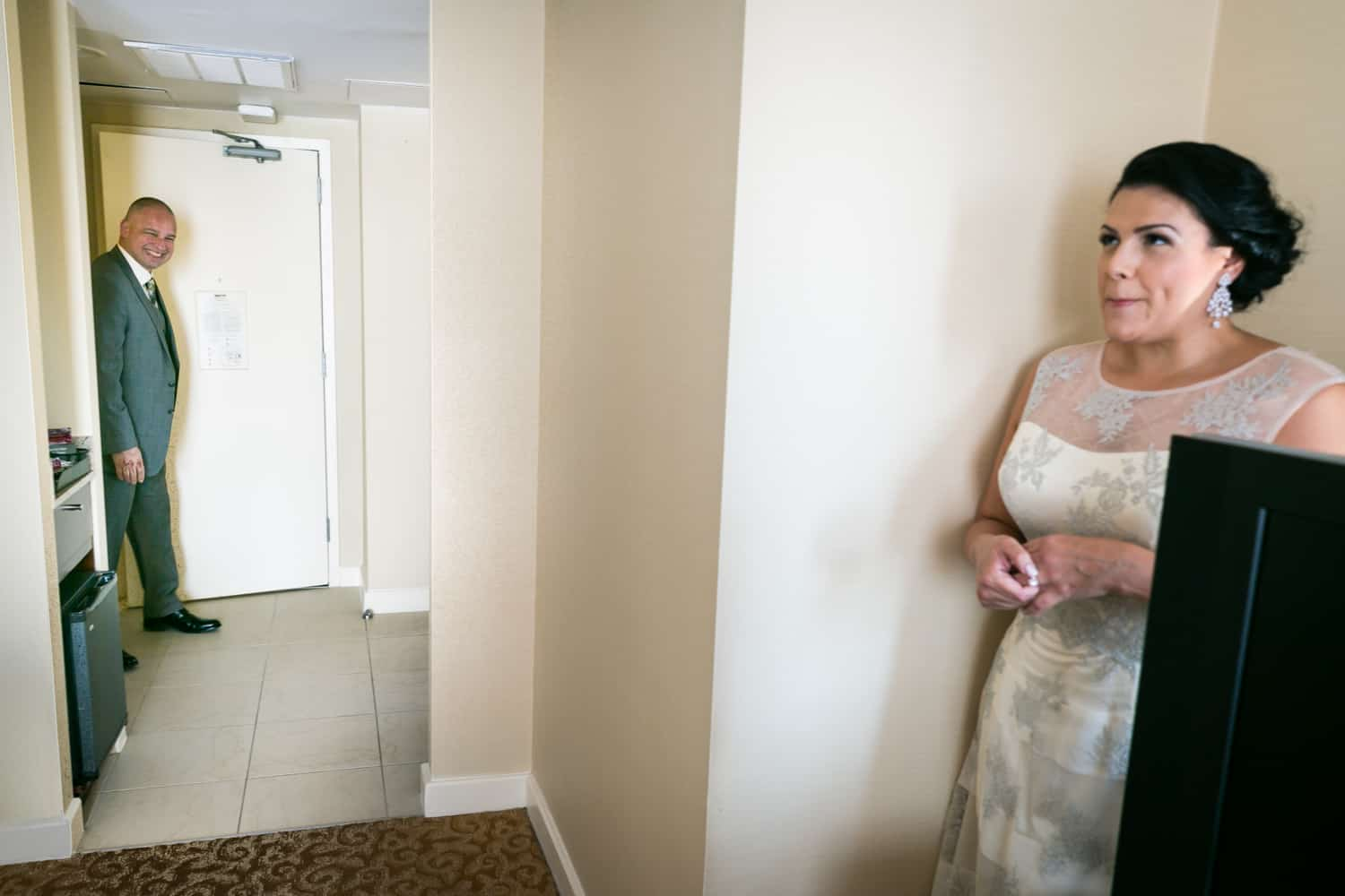 Bride hiding in corner of hotel room while groom walks in door