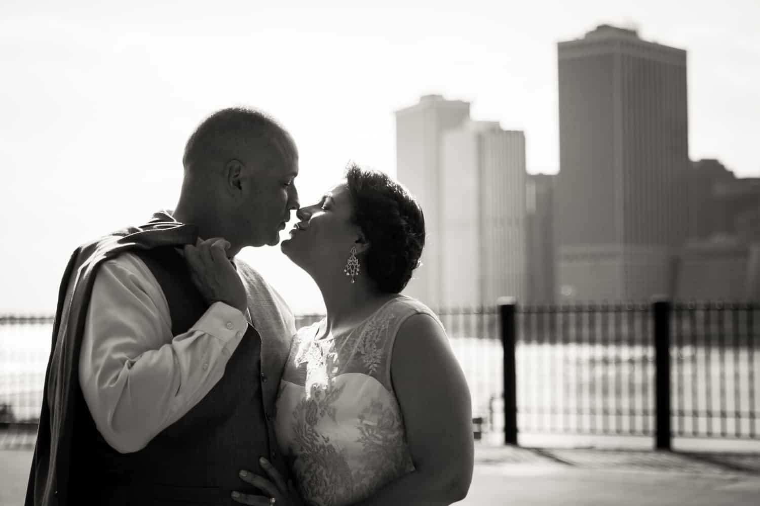 Black and white photo of bride and groom kissing on Brooklyn Promenade