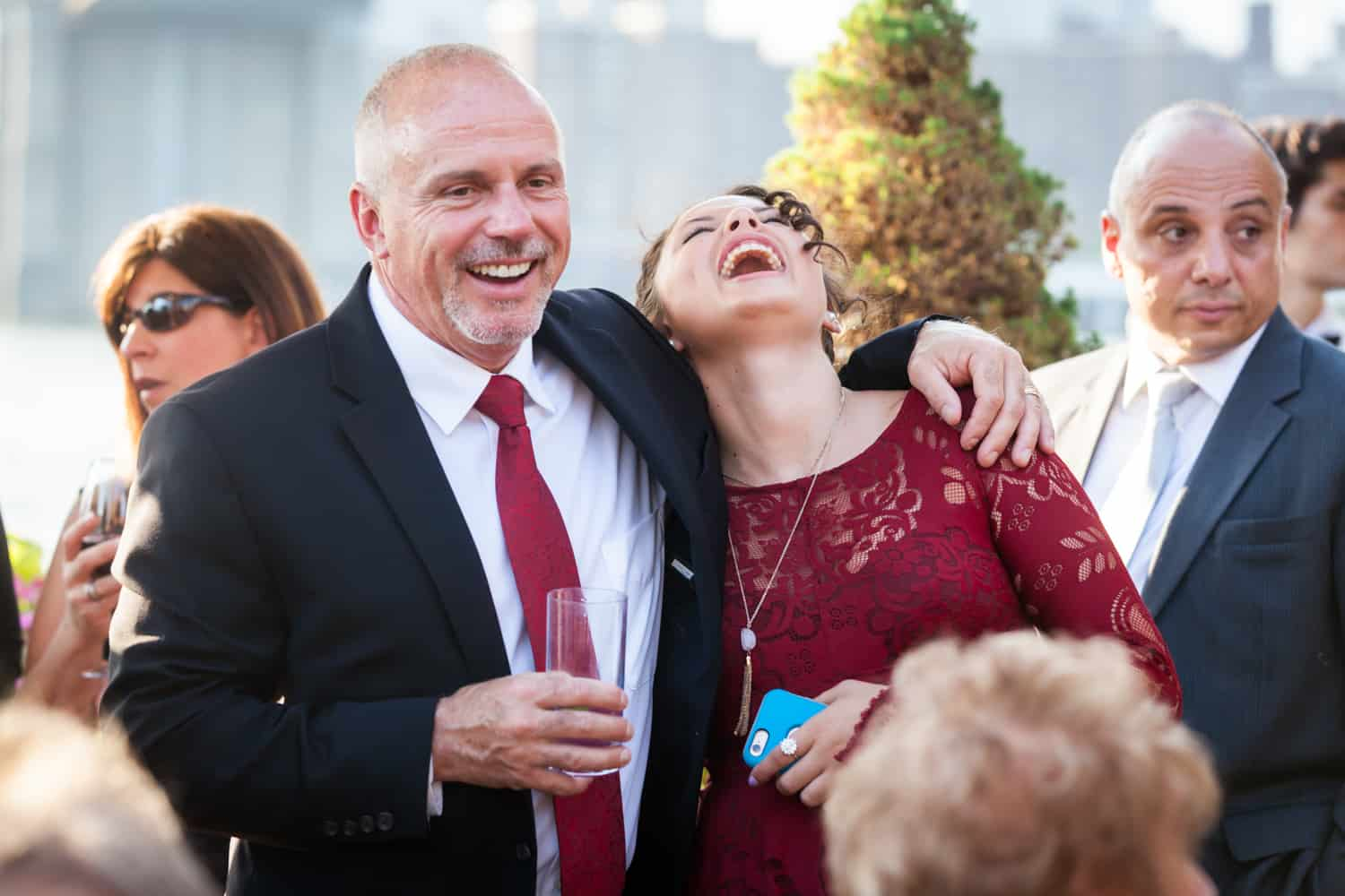 Two guests laughing at a River Café wedding in Brooklyn
