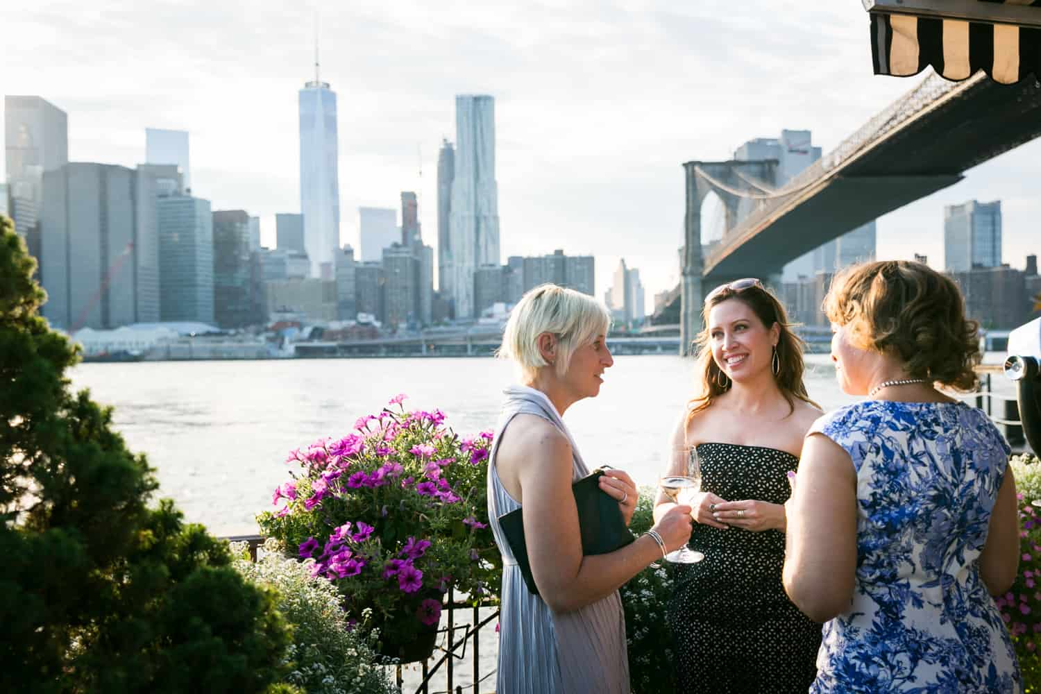 Three female guests chatting outside at a River Café wedding in Brooklyn