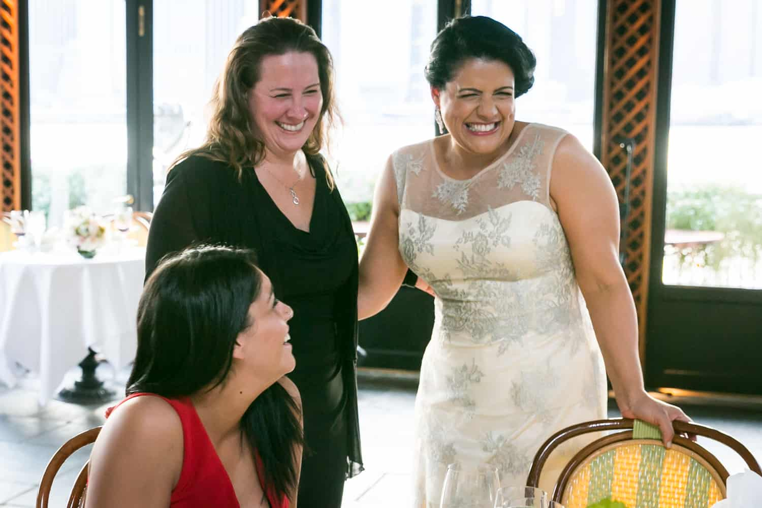 Bride chatting with two female guests at a River Café wedding in Brooklyn