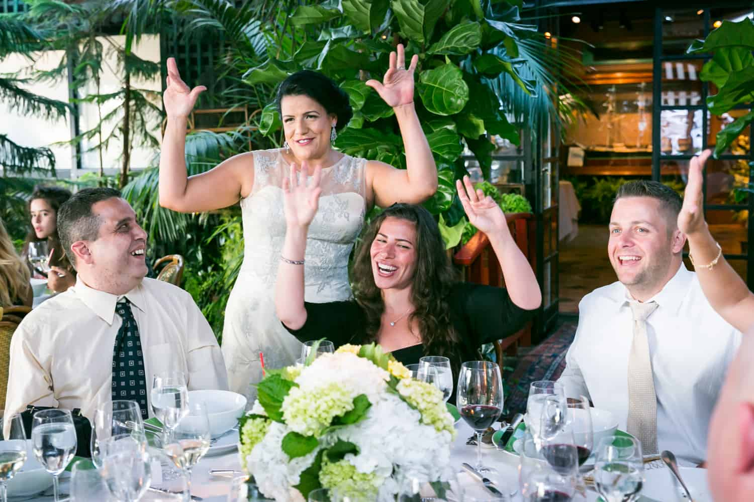 Bride raising hands with guests at a River Café wedding in Brooklyn