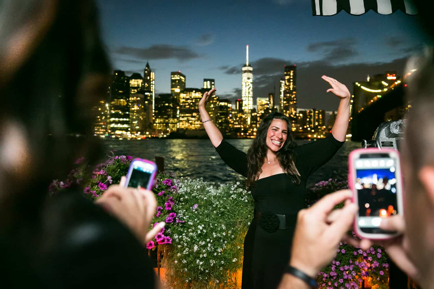 Female guest taking photo outside at night at a River Café wedding in Brooklyn