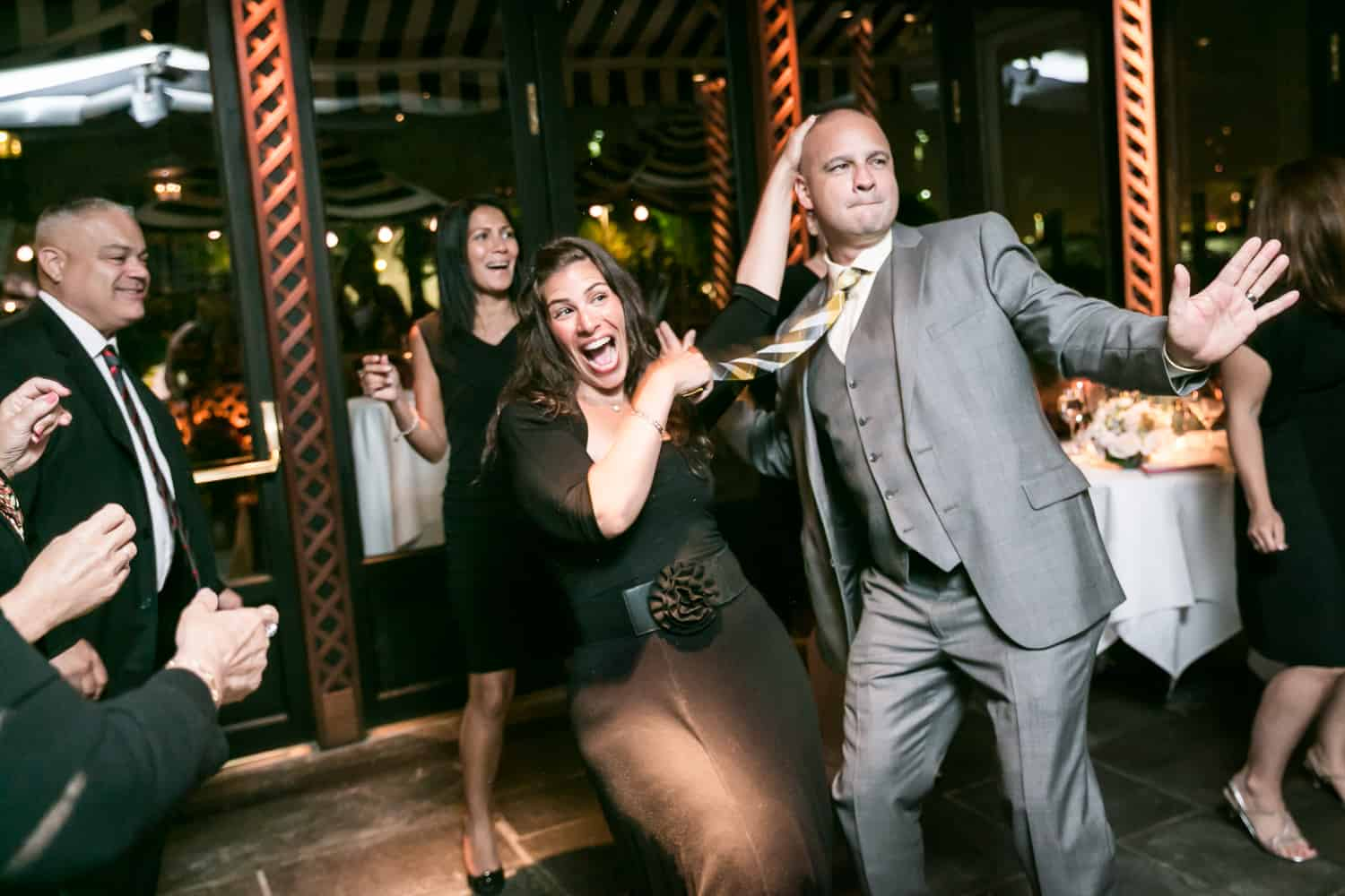 Female guest dancing crazy with groom at a River Café wedding in Brooklyn