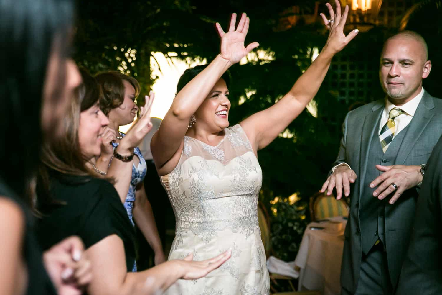 Bride dancing with arms raised at a River Café wedding in Brooklyn