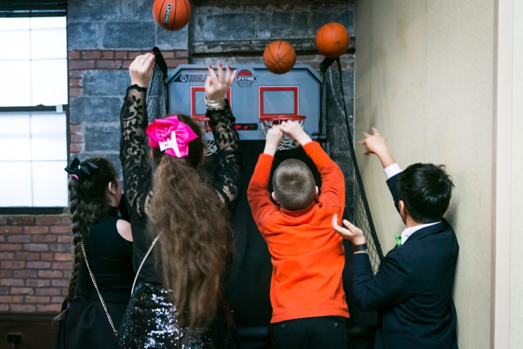Guests playing basketball at a Brooklyn bar mitzvah at 26 Bridge, by Brooklyn bar mitzvah photographer, Kelly Williams