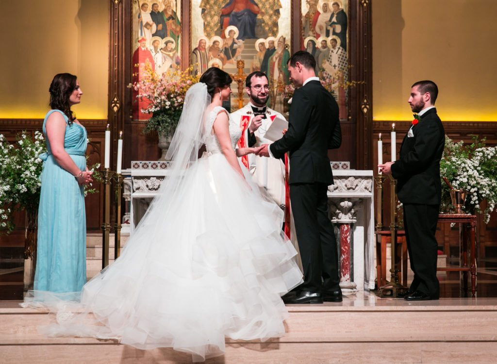 Exchanging rings at a Fordham University Church wedding ceremony