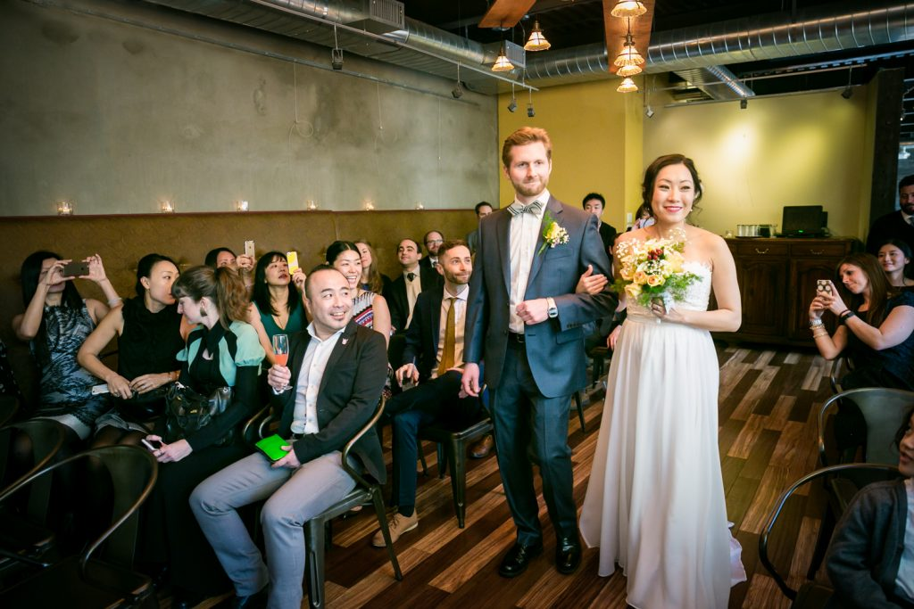 Bride and groom walking down aisle during ceremony at an Astoria restaurant wedding