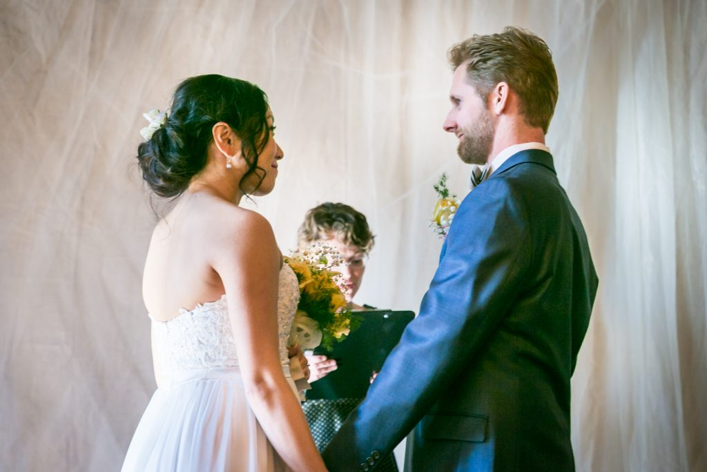 Bride and groom exchanging vows at an Astoria restaurant wedding