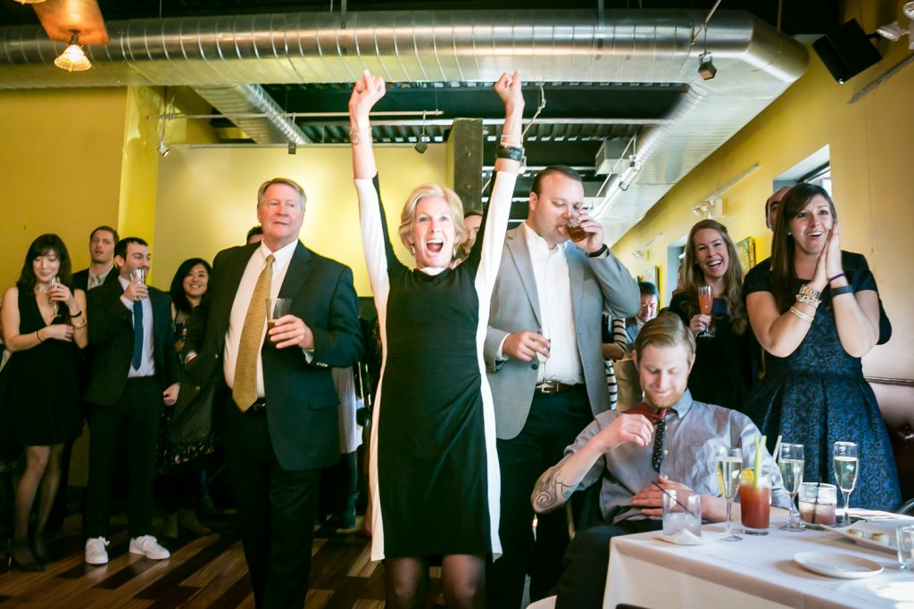 Woman cheering with arms raised at an Astoria restaurant wedding