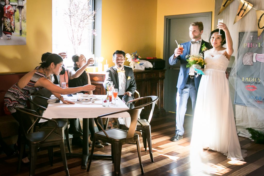 Bride and groom raising glasses with guests at an Astoria restaurant wedding