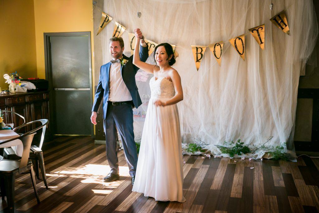Bride and groom raising hands at an Astoria restaurant wedding