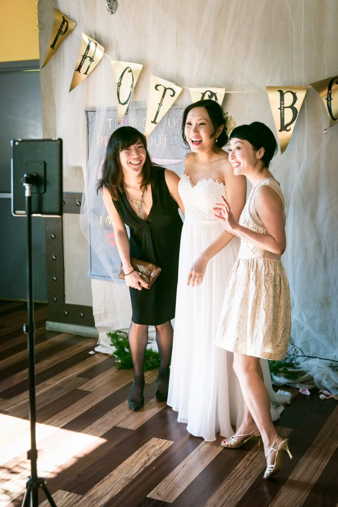 Bride and two girlfriends in front of DIY photo booth