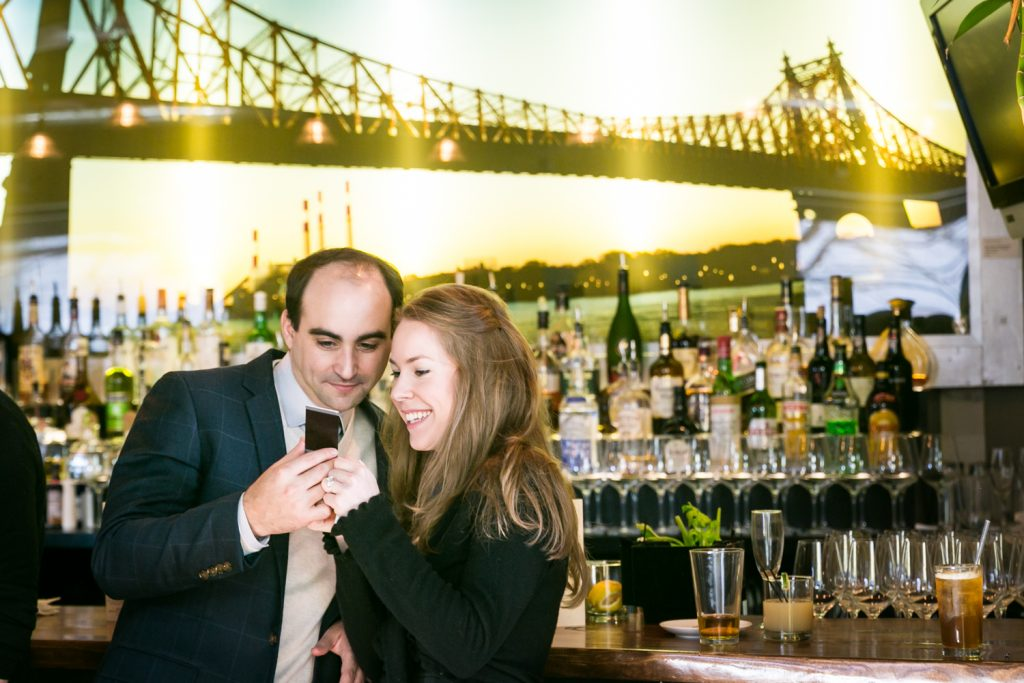 Couple looking at photograph in front of bar