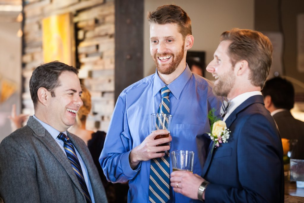 Three male guests laughing at an Astoria restaurant wedding