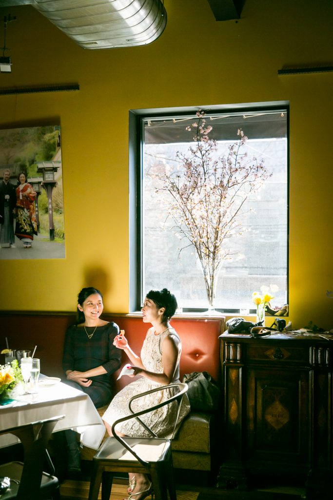 Two female guests seated and talking in front of window with large branch