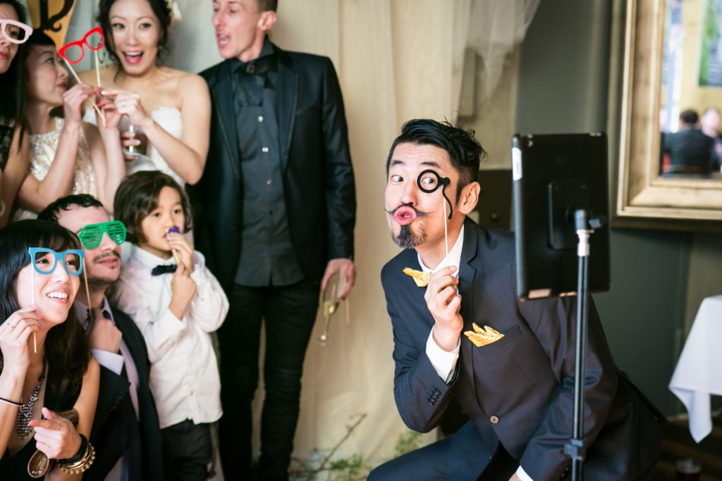 Guests clowning around in front of photo booth at an Astoria restaurant wedding
