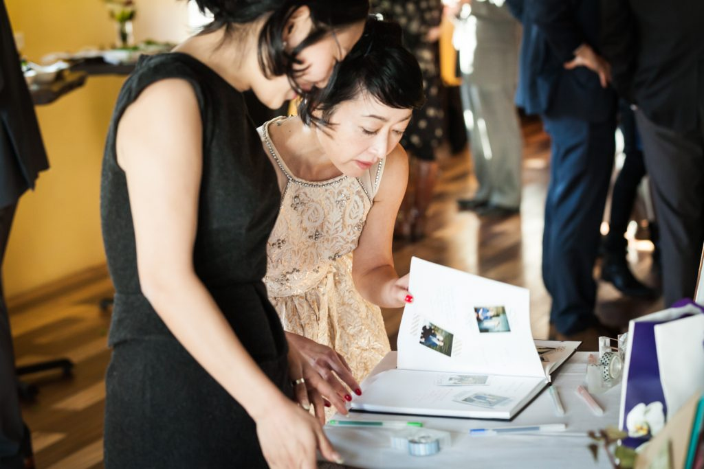 Two female guests looking through guest book