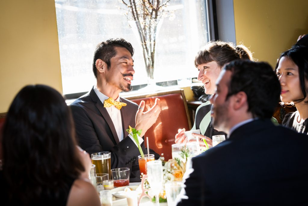 Guests talking in front of window at an Astoria restaurant wedding