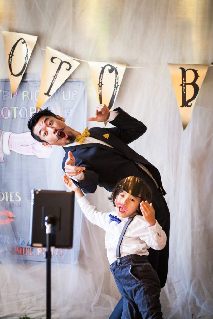 Man and boy playing in front of photo booth at an Astoria restaurant wedding