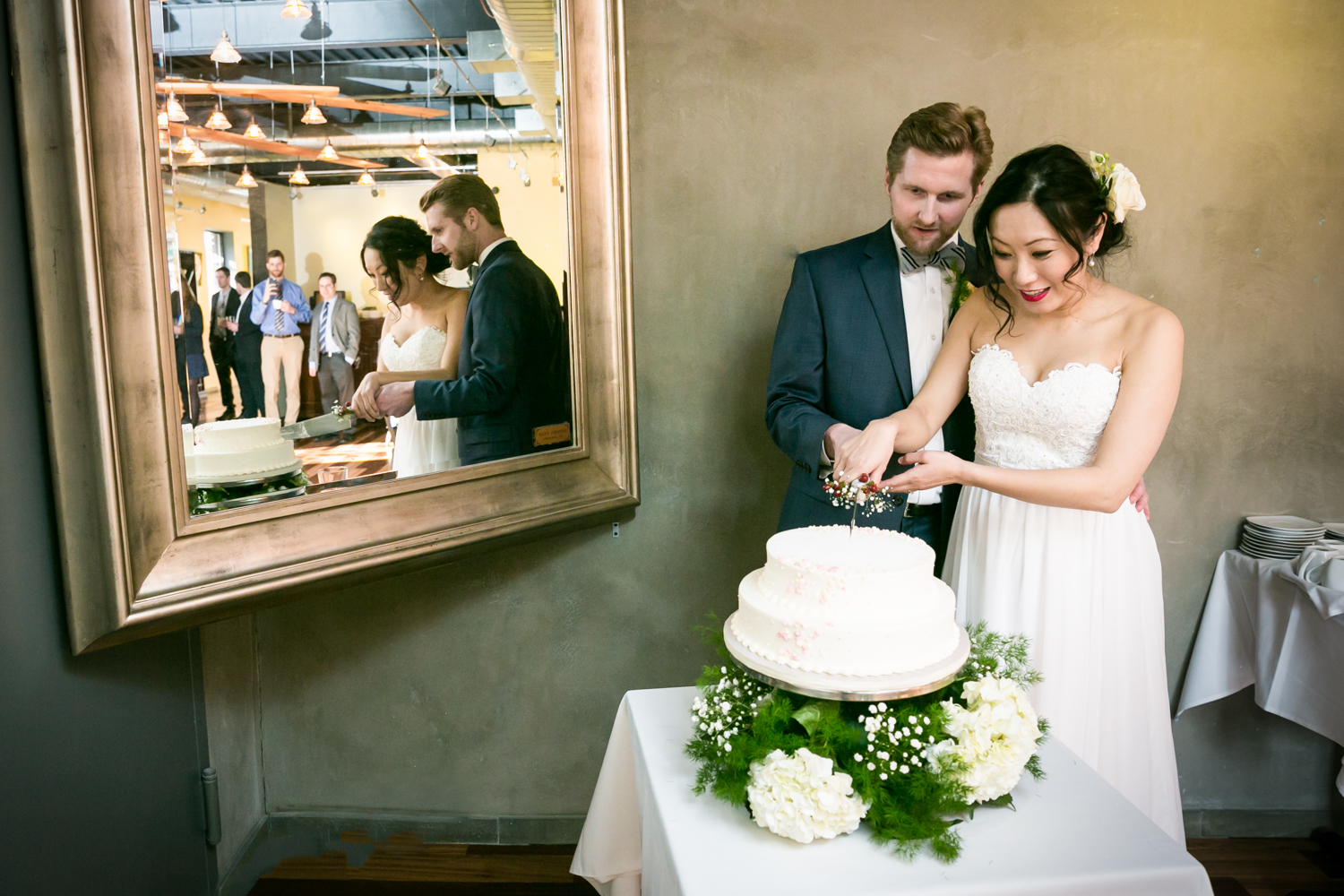 Bride and groom cutting cake with reflection in mirror