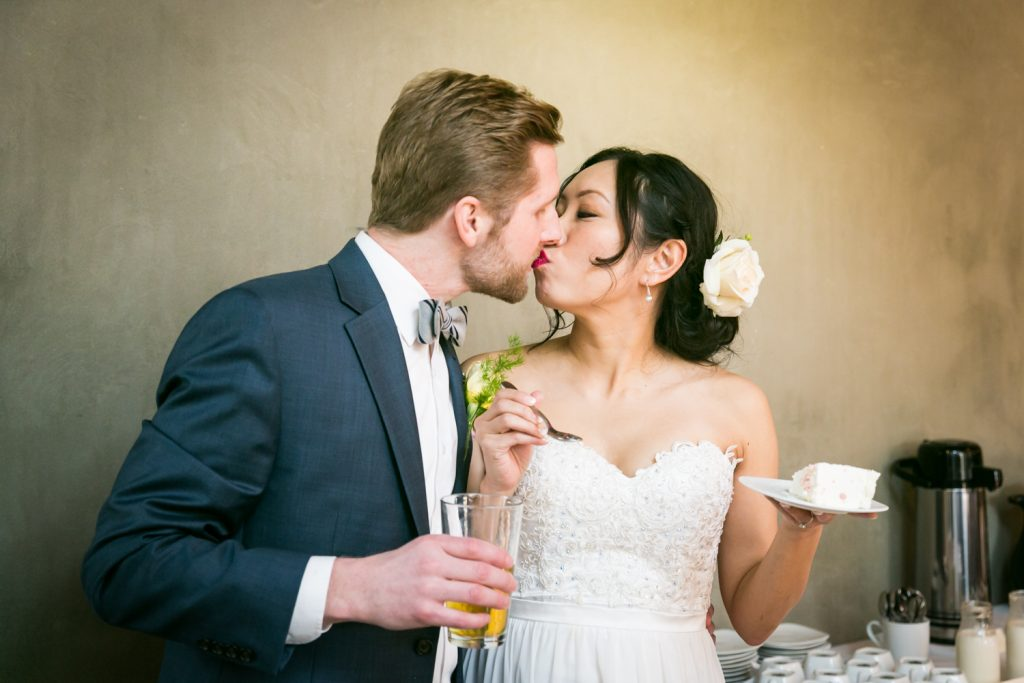Bride and groom kissing after cake cutting at an Astoria restaurant wedding