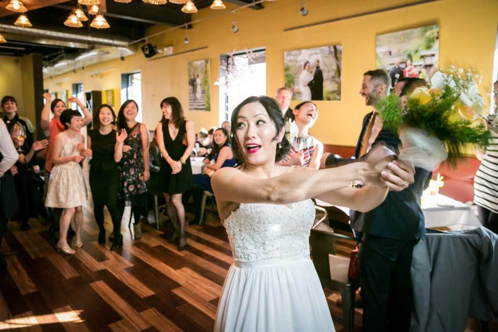 Bride about to throw bouquet at an Astoria restaurant wedding
